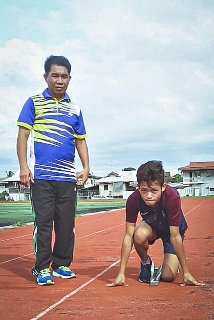 Azrul, an athlete with intellectual disability from Brunei, with his coach, Suhaili, on the tracks.