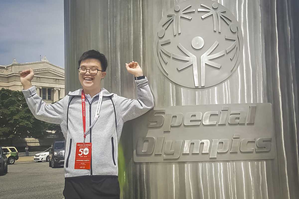 Johannes Cheong, Special Olympic Asia Pacific athlete, posing next to a Special Olympics logo.